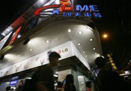 People walk past a GOME store at the shopping Mongkok district in Hong Kong June 22, 2009. GOME Electrical Appliances, a top China electronics retailer, announced on Monday that U.S. private equity firm Bain Capital has agreed to take up to a quarter of its shares under a plan to raise $418 million or more.   REUTERS/Bobby Yip   (CHINA BUSINESS)
